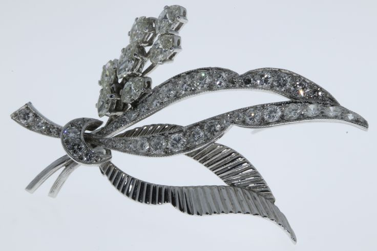 Lot 574, An 18ct white gold floral spray diamond brooch comprising seven elliptical stones and 39 brilliant cut stones in a bright cut mount, est  £400-600