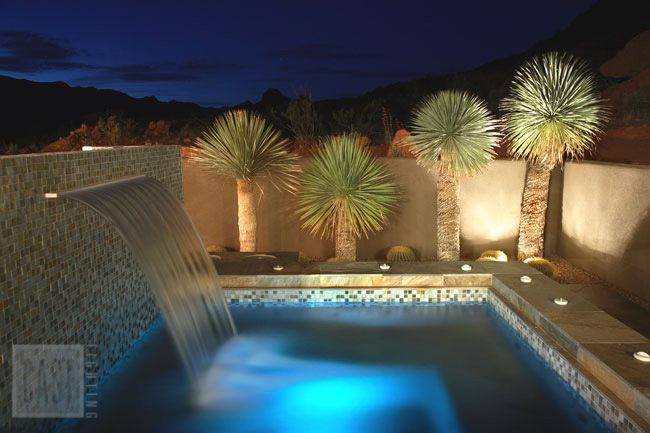 You can almost hear the waterfall cascading into this clean and modern southwestern pool design. Pin this landscape lighting look.