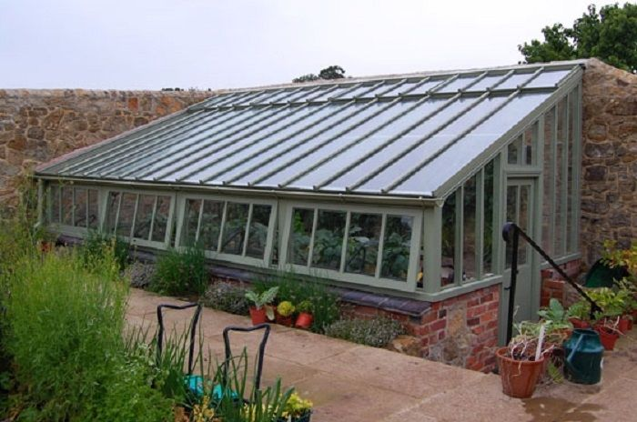 Semi-underground greenhouse surrounded on two sides with a stone wall and earth behind. www.solarinnovations.com