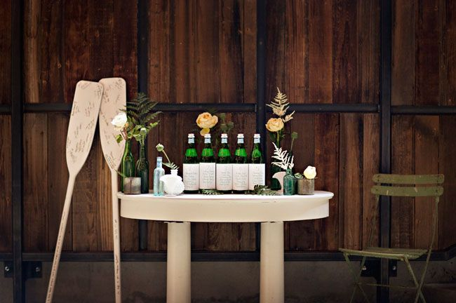 oar guest book, seating chart in calligraphy on bottles. From our Emerald Botanical Beach styled shoot.  Styled by Simply by Tamara Nicole. Courtney Bowlden Photography. Florals by Bash & Bloom.  Vintage Ambiance rentals.  Calligraphy by Ephemera Press.  Venue: Cast Iron Studios