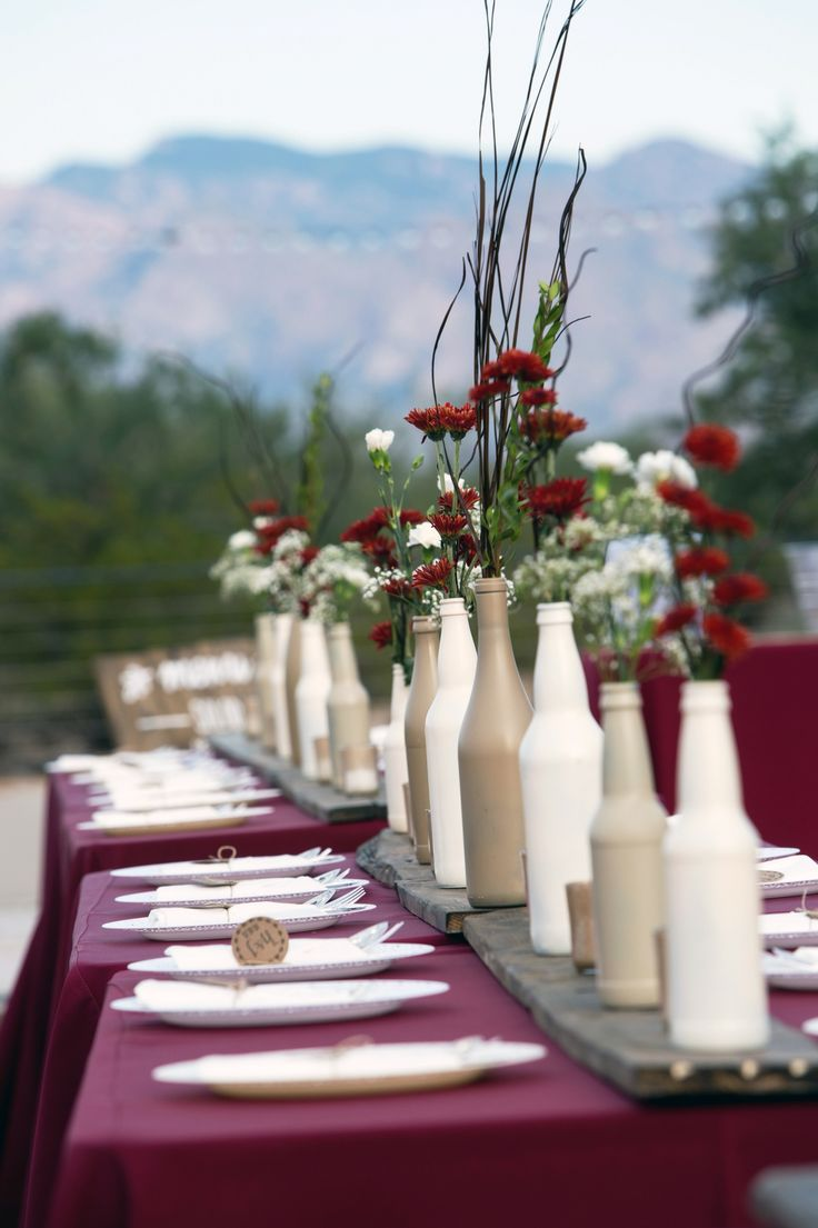 Burgundy and cream wedding. Bottle centerpiece so with wood runners. Mini carnations, babies breath, and poms.