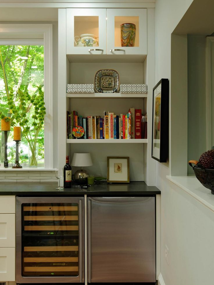 Stainless steel appliances, quartz countertops and a large, unadorned window are signs of contemporary design in this bright kitchen. A wine cooler and mini fridge are conveniently nestled by the pass-through bar, while a built-in bookshelf provides space for cookbooks and bar accessories.