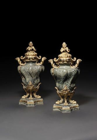 A pair of ormolu-mounted green marble urns and cov…