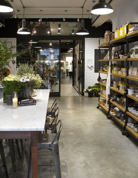 Rustic Retail Store Design - Open shelves of gourmet goods in a room with a marble-topped table and industrial bar stools