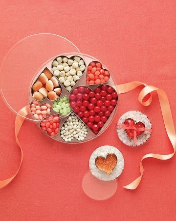 Heart shaped cookie cutters filled with candy placed inside of round containers for favors