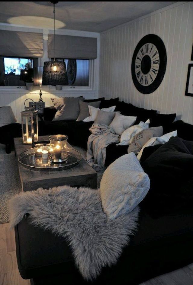 Black couch covered in gray pillows and fur throw create a comfy environment.