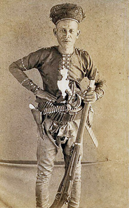 The indomitable Hadji Abdullah of Jolo (in the Philippines) with pearl-handled revolver and .30-.40 Krag gifted by Taft. The weird white shape at his solar plexus is what looks like the finely carved and highly stylized ivory kakatua pommel of his Kris. High status.