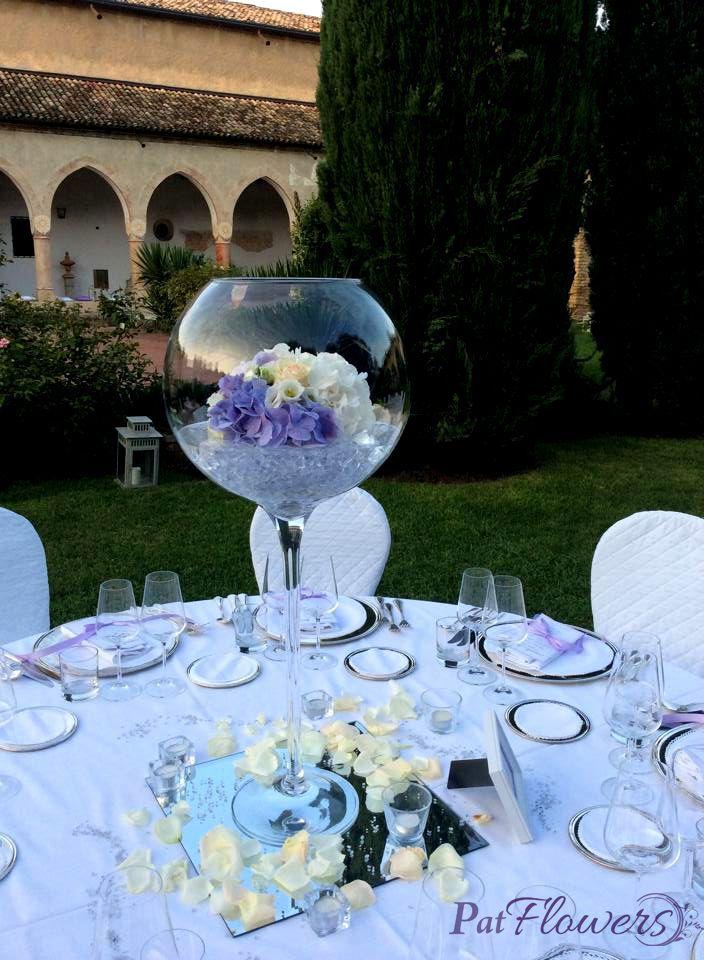 Romantica boulle in vetro, con cristalli e bouquet di ortensie bianche e lilla adagiate su un scintillante specchio contornato di petali di rosa bianca e t-light.