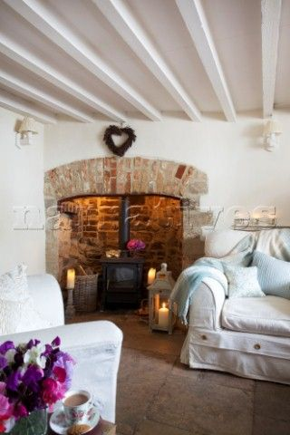 Exposed brick fireplace and white painted walls. cosy and comfortable