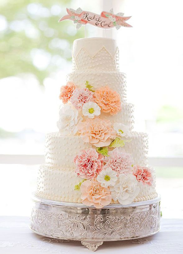 From the textural details to the pink and orange color palette, we're loving this fun take on a spring wedding cake. #springweddingcake