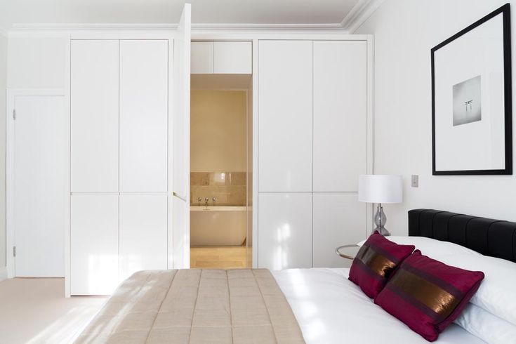 Lexham Gardens, Kensington - Granit Architects. Bright white space. Hidden door to Ensuite bathroom. Enticing and welcoming. Flat panel wardrobe doors makes joinery disappear.