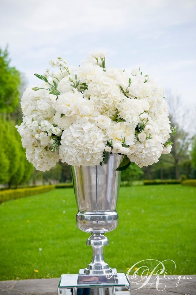 A metallic vase with simple white floral creates a statement piece.