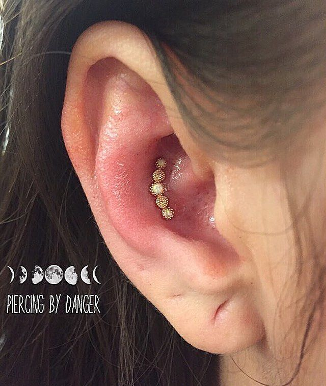 Rose Gold Milgrain nd Opal Cresent in Fresh Ear conch piercing.  Jewelry by Body Gems. Piercing done at Energy Tattoo by Kara Danger