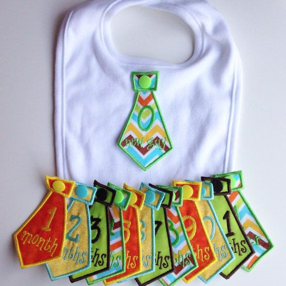 Baby Boy Monthly Milestone Bib Tie Set  One white cotton bib with 13 interchangeable handmade embroidered monthly milestone ties.  Ties: 0