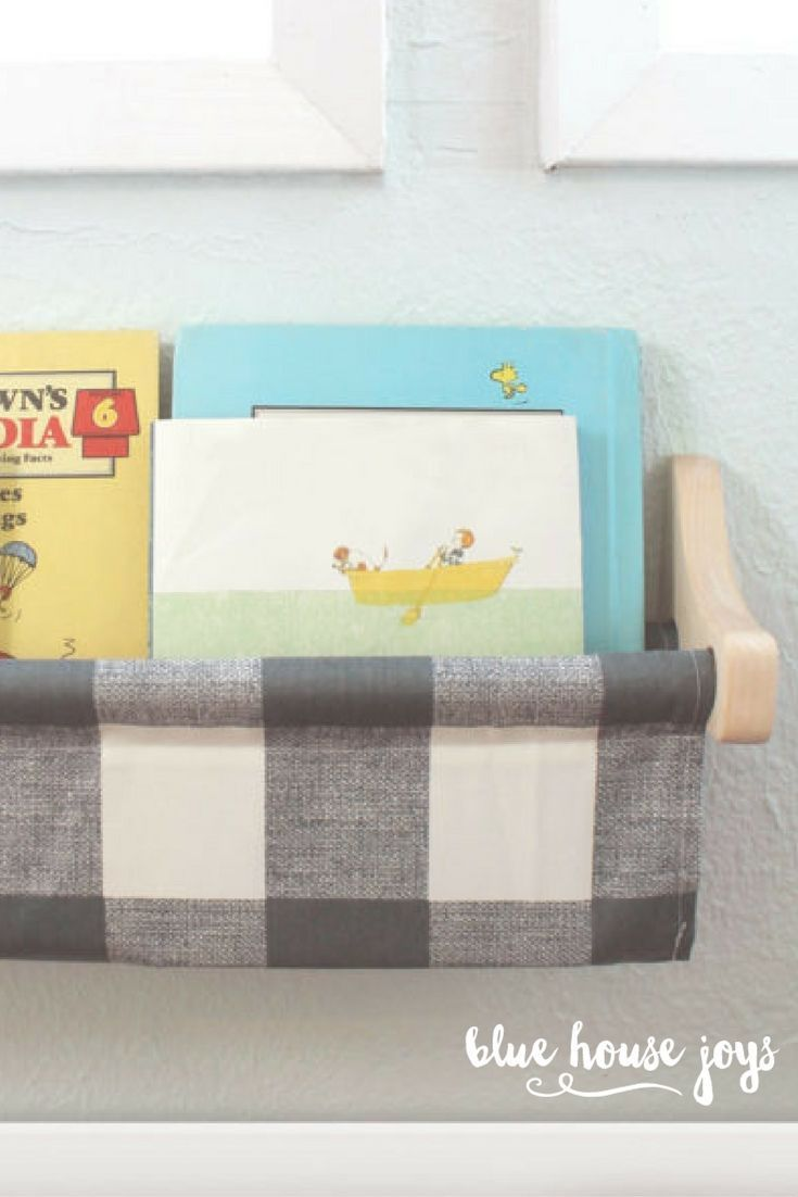 A stylish and inexpensive book sling in the popular buffalo check print to store your kids' books. Hang this up at any height and give your child a simple way to grab their favorites for a quick read. Choose from maple or white brackets. Perfect for playrooms, nurseries, and kids spaces. Visit our shop at bluehousejoys.com/shop/ for more inspiration!