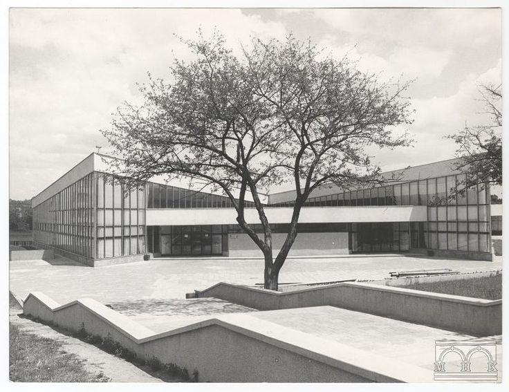 Fotografia czarno-biała przedstawia modernistyczny budynek o nieregularnym kształcie. Na pierwszym planie widać schody idące ukośnie z prawej do lewej i trawniki. W centrum drzewo okryte młodymi liśćmi, a za nim gmach o dwóch nachylonych do siebie skrzydłach połączonych przełaczką. Na odwrocie w prawym dolnym rogu numer 000026. Zdjęcie przedstawia największą w Nowej Hucie stołówkę pracowniczą na 2000 osób, znajdującą się na os. Złotej Jesieni. Obecnie znajduje się tam sklep