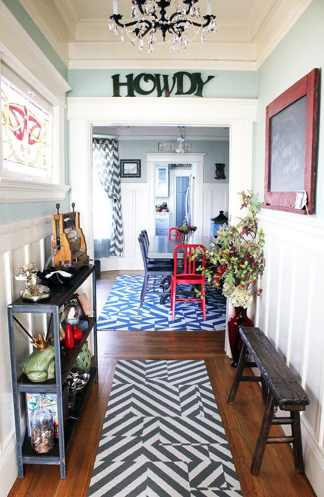 "Add originality to your home with an entryway that pops with eclectic details, from the chandelier to the ""Howdy"" sign to the patterned rugs. Color, texture, and pattern are what add personality to a space."