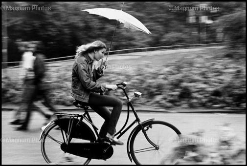 Gilles Peress NETHERLANDS. Amsterdam. 1971. Girl on bike with umbrella.