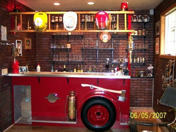 A unique bar in a family room remodel. Any firefighter would love to have this bar a mockup of an antique fire engine. Complete with lots of brass diamond plate red lights a brass bell even a hose bed.