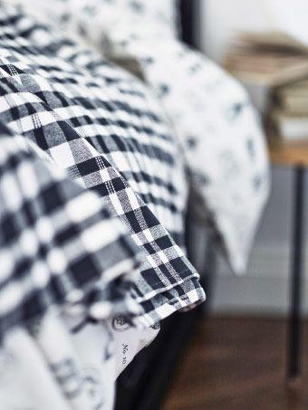 Ein Bett, abgedeckt mit BACKVIAL Tagesdecke in Schwarz/Weiß