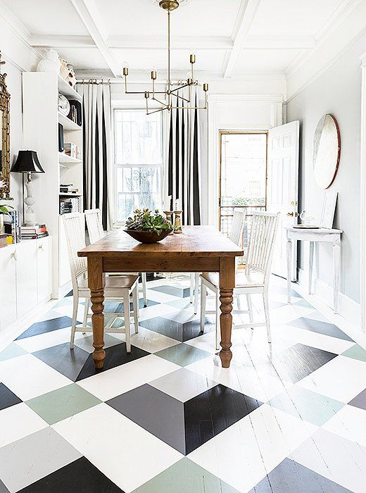 The finished tumbling blocks pattern painted floor adds such a whimsical, Scandinavian-inspired charm to this monochromatic dining room.