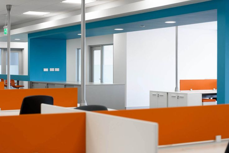 Orange and white office desk dividers with grey service poles and blue snake feature forming printing station.