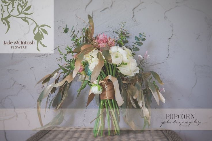 Long, gold-tipped gum leaves finish off this loose and unstructured bouquet, bound in copper ribbon.
