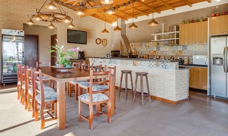 O piso de porcelanato e o forro inclinado de madeira são a base do espaço gourmet. O balcão da churrasqueira foi revestido com tijolos ecológicos e ladrilhos de porcelanato e o tampo é de granito preto no projeto da arquiteta Juliana Lahóz, para o lazer de uma casa em Araucária, no Paraná