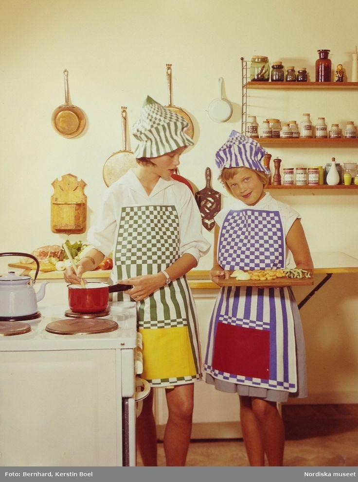 Två flickor med färgglada randiga förkläden i kök, ca 1958-1962. Foto: Kerstin Boel Bernhard