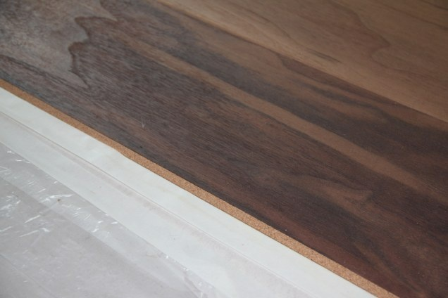 Podłoga warstwowa Scheucher - orzech amerykański. Dylatacja z korka na styku dwóch rodzajów podłóg.