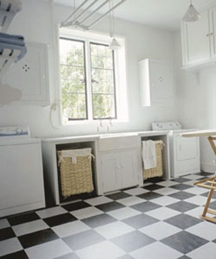 laundry room baskets - large manor house laundry room with a pair of hotel-size laundry baskets on casters in built in openings flanking the sink - Plain English via Atticmag