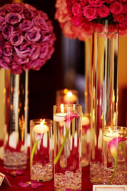 Centros de mesa con jarrones cilíndricos de distintas alturas, para darle profundidad a la decoracion de la mesa. #CentroDeMesa con cartuchos y pétalos de rosas rojas y rosadas