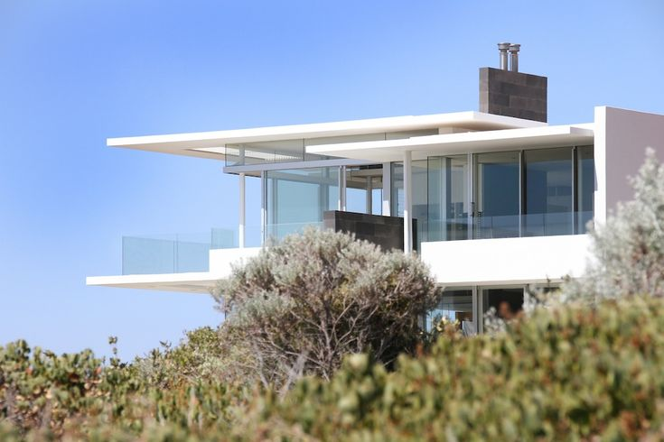 "Project Summary: ""Conceived as a series of interlocking horizontal planes, this beach house is set comfortably within the sand dunes overlooking Avalon Bay. A low slung profile blends into the landscape. Entering the house through a large pivot door into this double story space, the relationship between line, volume and horizon comes into focus. Lines extend through the house all converging to the distant horizon."