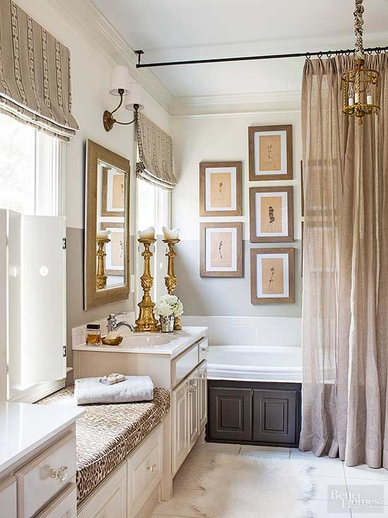 Introduce warm neutral color into your bathroom with accessories. Here, pleated burlap curtains, a leopard-print bench seat, and botanical artwork, all in shades of brown, pop against light beige walls. Dark paint on the built-in bathtub grounds the look./