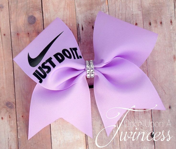 "This Nike cheer bow has a rhinestone center and is set on a seamless hair tie. It is full size at 7""x7""."