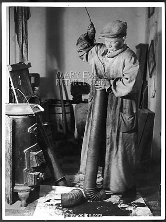 A young chimney sweep cleans the pipe of a stove with his brush.