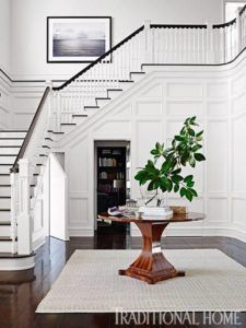 This is an inspiration for a simple white-paneled foyer with brown wood round table and plush rug in the center. The dark-toned brown floor provides an interesting contrast with the white color of the wall and of the formal-styled stairs. The planter with shrub sits as the centerpiece of the table. Source: traditionalhome.com