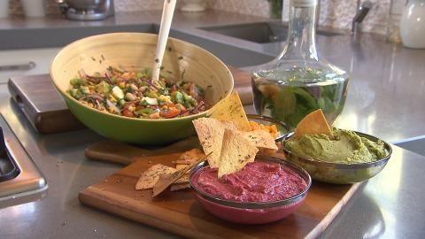 Sharon maakt een paarse, een groene en een oranje hummusvariant bij heerlijke nacho's en een bonensalade.