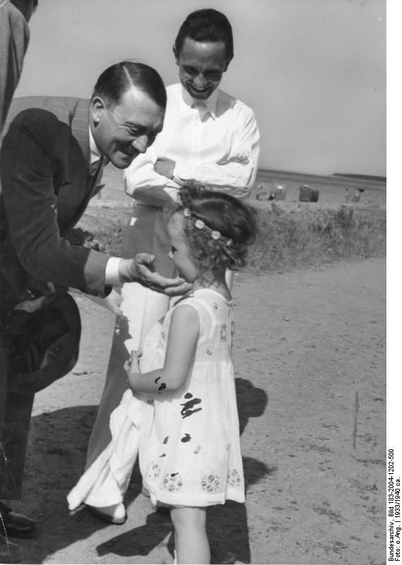 Adolph Hitler, Joseph Goebbels and one of Goebbels' daughters. The Goebbels would later commit suicide and murder all 6 of their children as the madness of the 3rd Reich collapsed around them.