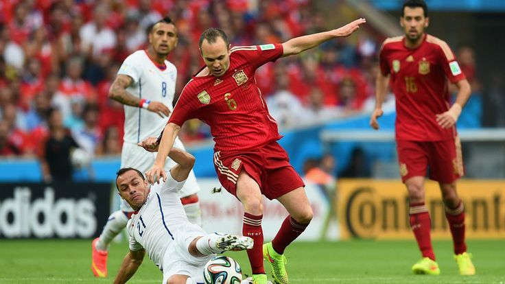 Andres Iniesta of Spain is tackled by Marcelo Diaz of Chile