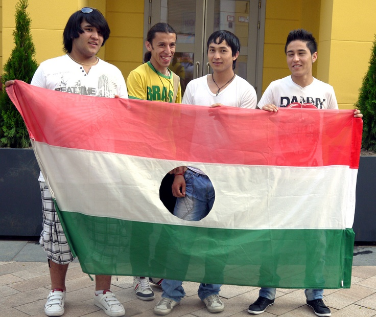 A group of young Afghan refugees pose with the 1956 revolutionary Hungarian flag in Budapest, at an alternative history class at the occasion of World Refugee Day.© UNHCR/Z.Toth/June 2011