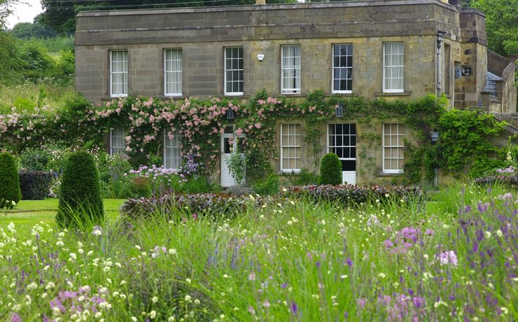 Roses spilling over the door and a delicate meadow in the foreground. Arne Maynard Garden Design