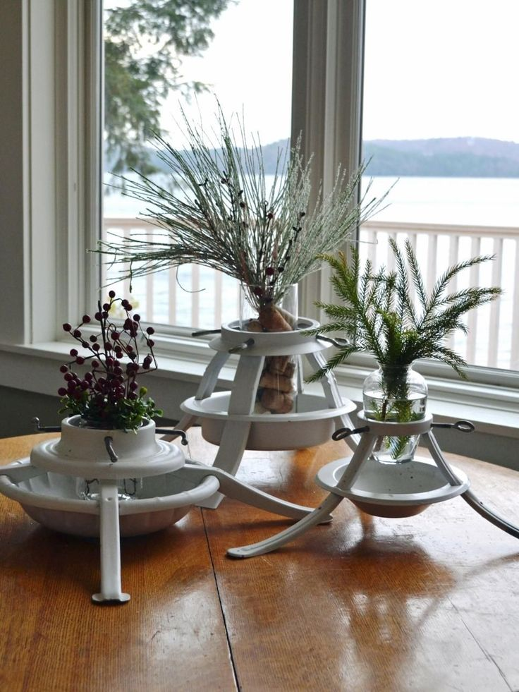 Old tree stands are plentiful at thrift stores and garage sales. Grab a trio and turn them in vase holders. We spray painted these white, added glassware then filled them with holiday flowers, evergreens and berries.