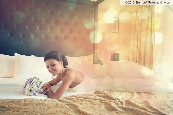 Bride lays on a bed in a newweds room