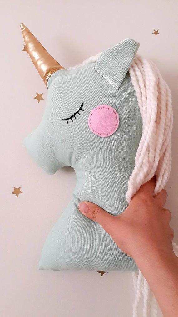 Almohadilla de la felpa unicornio llevará magia a su habitación de los niños. Este unicornio hermoso mint tiene un cuerno brillante y blanca melena de lana muy suave. Las mejillas son cosidas con cuerda plata de fieltro rosa y ojos son bordado a mano. Medidas de 15.5 pulgadas (39 cm). Este es un elemento decorativo y listo para enviar. También puedes ver rosa unicornio https://www.etsy.com/listing/267736646/unicorn-pillow-plush-toy-pink-unicorn?ref=shop_home_...