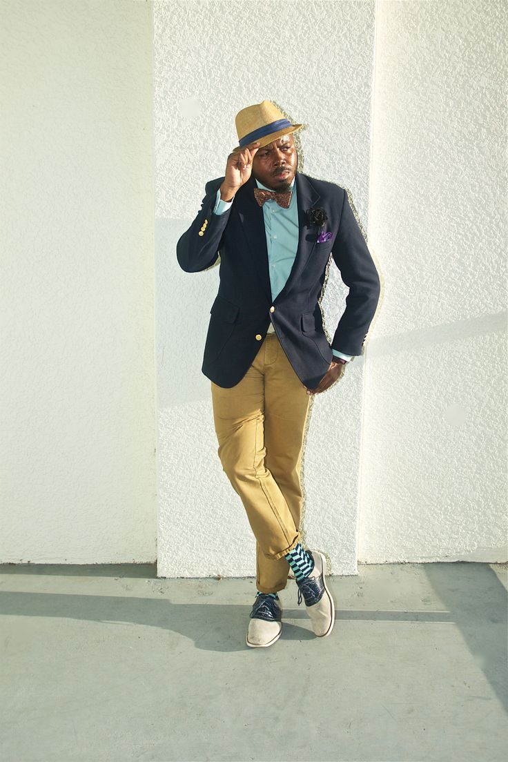 Tan fedora with a dark blue brim, dark blue blazer, turquoise shirt, purple and tan bow tie, black flower, purple pocket square, light brown pants and gray and blue saddle shoes.