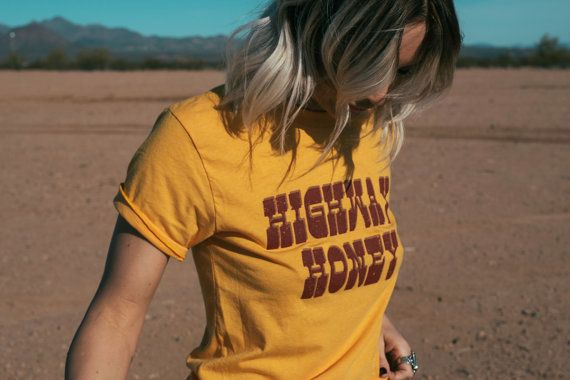 Our Highway Honey tee is made with 70s inspired, marigold yellow tee, with burgundy and brown print. Sizing is unisex, meaner a looser womens fit.
