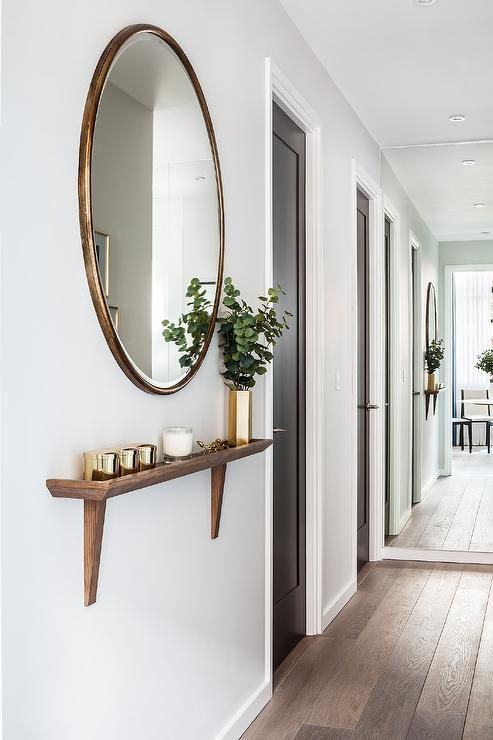 Chic foyer hallway features a round gold oversized mirror placed over a walnut stained wood wall shelf with wood brackets.