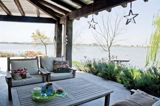 Una casa para disfrutar con todos los sentidos  La terraza con vista a la laguna, uno de los ambientes preferidos de la casa. Juego de sillones con colchonetas blancas y mesa de teca (La Española)..