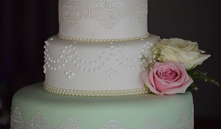mint green and off white wedding cake with Edible lace Details (Crystal Candy) and hand piped royal icing pearl detail. Decorated with fresh Flowers